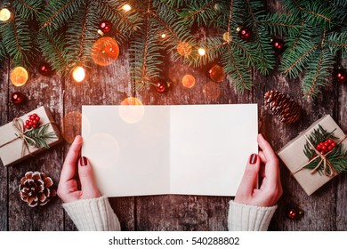 Female hand writing and reading a letter to Santa on wooden background with Christmas gifts, Fir branches and candy. Xmas and Happy New Year card. Flat lay, top view