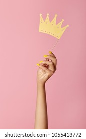 Female hand with yellow manicure hold a paper  craft crown on a stick. Isolated on a pink background. Beauty salon concept.