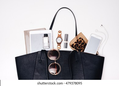 Female Handbag Content. Phone, sunglasses, make up and other stuff coming out of the bag.