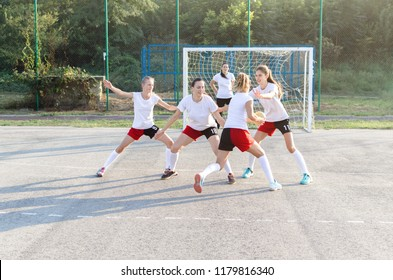 Female handball players are playing game outside.