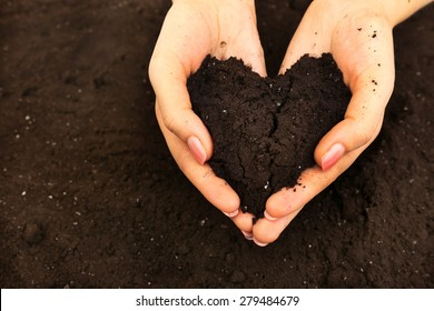 Female handful of soil in shape of heart, closeup