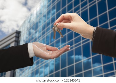 Female Handing Over the Keys to Other Woman in Front of Corporate Building.