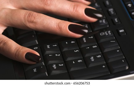 Female hands against the keyboard