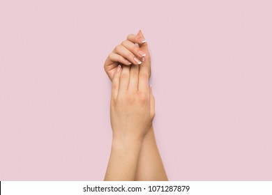 Female hands applying cream at pink background. Beauty, tenderness and skincare concept, copy space