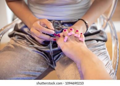 Female hands applying gel varnish on toenails