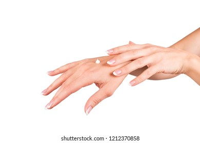 Female hands applying hand cream, white background, closeup and french manicure.