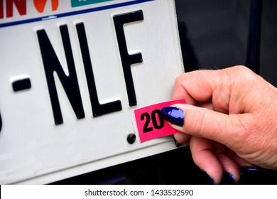 Female hands applying license plate registration annual sticker on white plate with black letters.