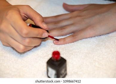 Female hands applying red nail polish