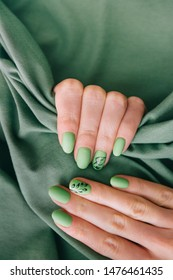 Female hands with art nails design and summer style manicure of green color on cotton fabric background.