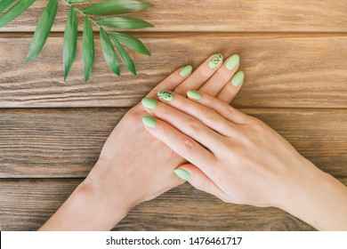 Female hands with art nails design and summer green stylish manicure near palm leaf on wooden background. Point of view in first person.