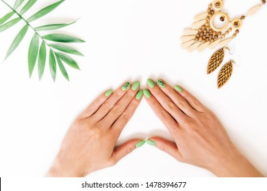 Female hands with art nails design and summer green color manicure near palm leaf and wooden handmade jewelry on white background. Point of view in first person.