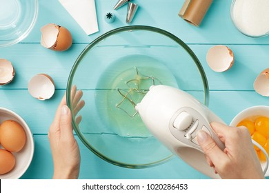 Female hands beating egg whites cream with mixer in the bowl on blue wooden table. Step by step recipe meringue cookies top view.