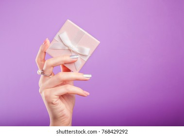 Female hands with beautiful manicure holding a small gift box on violet background.