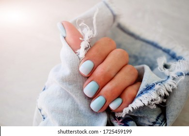Female hands with a beautiful manicure on a jeans background. Summer trend, blue gradient on the nails with gel polish, shellac. Short nails
