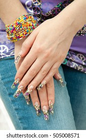 Female hands with beautiful multicolored manicure closeup on background of jeans.