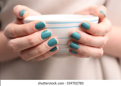 Female hands with beautiful nail art holding bowl, closeup