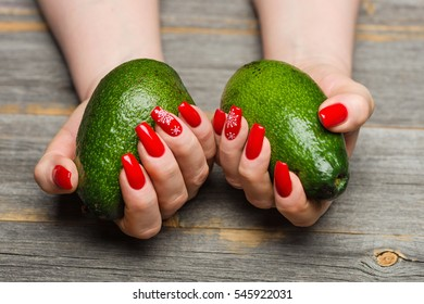 Female hands with beautiful New Year's manicure keep avocado fruits in style a rustic