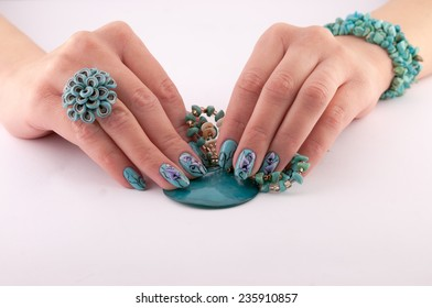 female hands with beautiful painted nails and jewelry on a white background