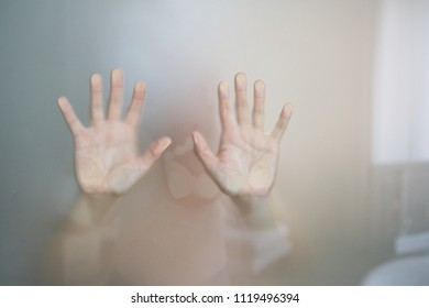 Female hands behind the glass in the bathroom. Abstract photo.