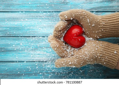 Female hands in beige gloves holding red heart