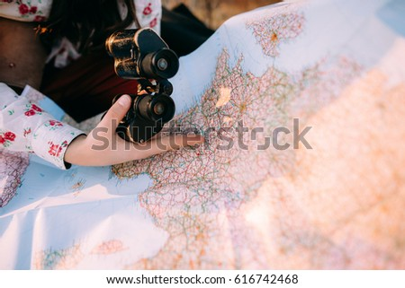 Female hands with binoculars choose a place on the map in warm light at sunset on the grass. Concept travel adventure. top view