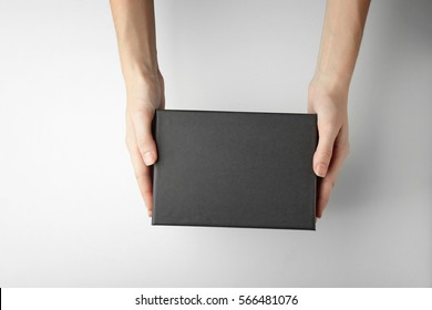 Female hands with black box on white background