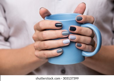 Female hands with blue cup