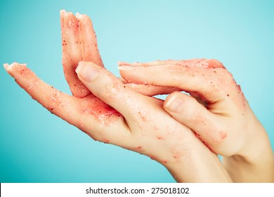 Female hands in body scrub on blue background