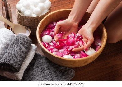 Female hands in bowl of spa water with flowers, hand care in nail salon, relaxing