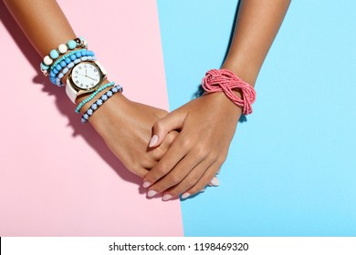 Female hands with bracelets on colorful background