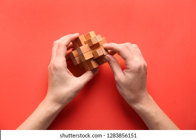 Female hands with brain teaser on color background