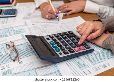 Female hands with calculator on 1040 tax form