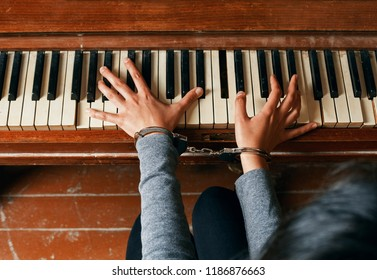 female hands in chains on a piano