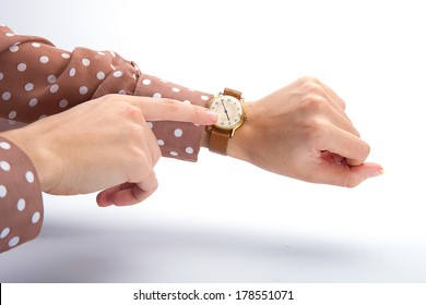 Female hands checking the time on a wristwatch.