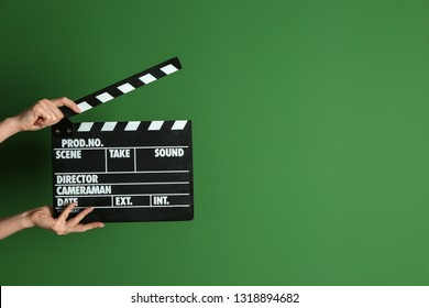Female hands with cinema clapperboard on color background