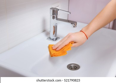 Female hands cleaning tap with orange cloth. Spring cleaning, washbasin