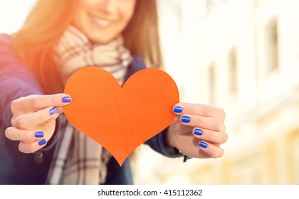 Female hands close up. Red heart in the hands. Woman and mark heart. Heart, love symbol young happy woman hold. Blurred people.