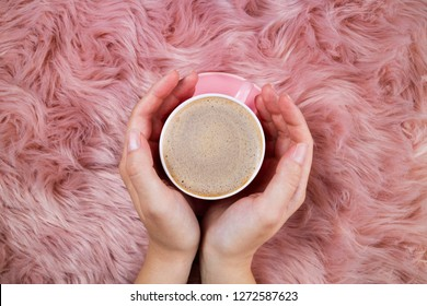 Female hands and coffee cup on pink woolen fur. Femininity trendy background. Morning coffee, breakfast, weekend and cozy atmosphere concept