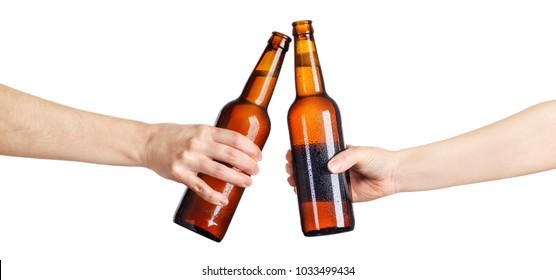 female hands with cold beer brown bottles making toast isolated on white background