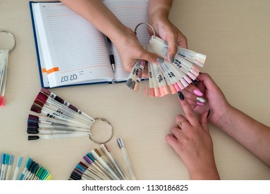 Female hands and colorful nail polish palette