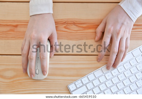Female hands with computer mouse and keyboard on wooden table