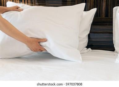 女性的双手纠正枕头在床上。 在酒店房间或家里准备床的概念