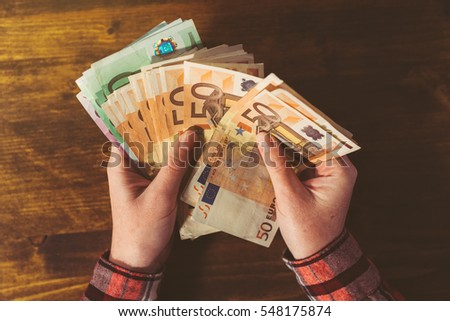 Female hands counting large amount of euro currency cash banknotes, top view above office desk