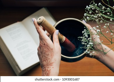 Female hands covered with henna tattoo holding tibetan singing bowl over the open book on a flower background. Meditation and inspiration mood