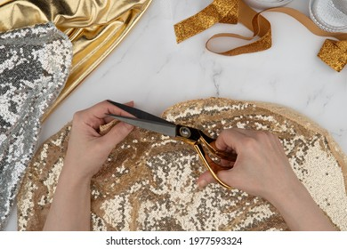 Female hands crafting clothes. Cut and sew customized garments. Gold scissors, threads, fabrics on a marble table. Sewing feminine, festive, glamorous, evening, wedding dresses, bridesmaids dress.