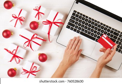 Female hands with credit card, laptop, christmas presents, red decor on white table flat lay, copy space. Business christmas holidays concept, holiday online shopping concept. Christmas shopping