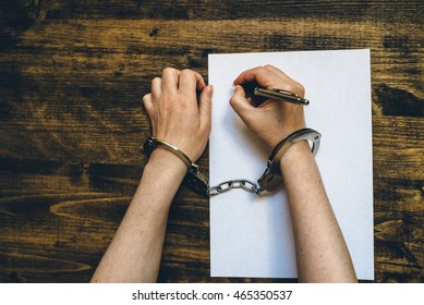 Female hands cuffed signing confession, top view of police investigator detective desk