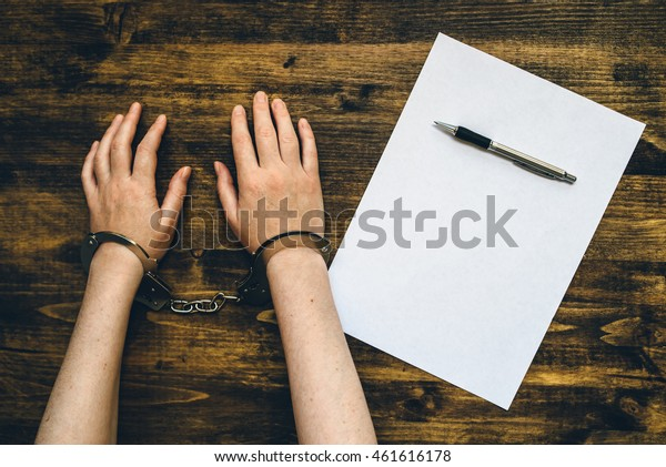 Female hands cuffed, top view of police investigator detective desk with pencil and blank paper for statement