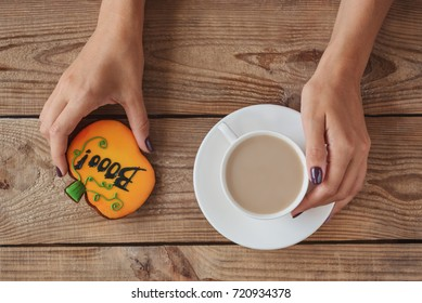 female hands, cup of coffee and biscuits with inscription booo on a wooden background, top view, concept halloween