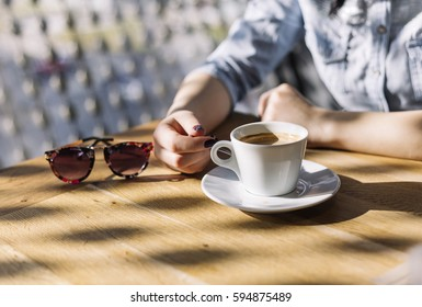 Female hands and cup of coffee with sunglasses on rustic wooden table background. Business woman indoor with coffee.